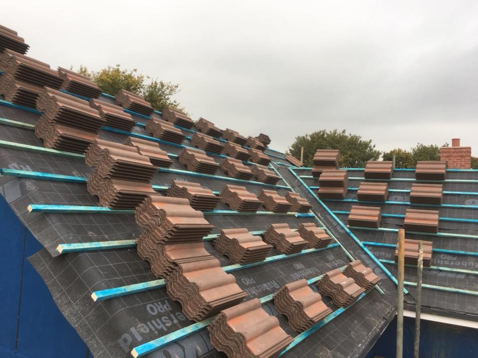 A new roof is installed in the UK with plain red clay tiles